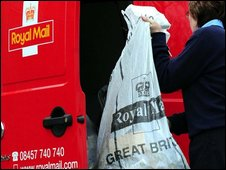 Royal Mail worker lifting a bag of letters into a van
