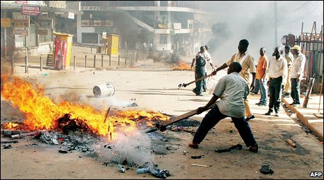 People attempt to put out fires during riots in Kampala, Uganda (10 September 2009)