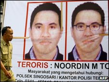File pic of Indonesian policeman walking past wanted poster of Noordin Top
