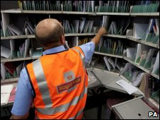 Postal worker sorting letters at a Royal Mail delivery office
