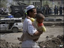 An Afghan man holds his son, after they both sustained minor injuries following a suicide car bomb attack on an Italian military convoy, near the site in Kabul, Afghanistan, Thursday, Sept. 17, 2009.