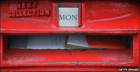 Letters overflow from a postbox in Lacock