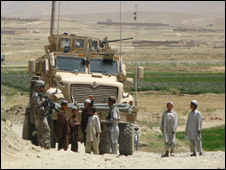 Afghan boys stare at  a US Army mine resistant vehicle
