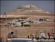 Workers lay the foundations of a new house in the Israeli settlement of Tekoa in the West Bank, 7 September 2009