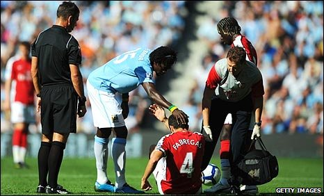 Emmanuel Adebayor offers his hand to Cesc Fabregas after fouling his ex-team-mate