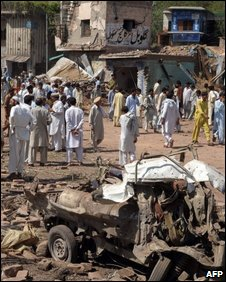Pakistani local residents gather at the wreckage of a market and vechiles after a suicide car bomb blast near the garrison city of Kohat on September 18, 2009