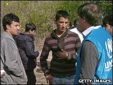 Member of the UN Refugee Agency (UNHCR) speaks with migrants