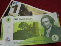 One Lewis pound lying on top of one Brixton pound