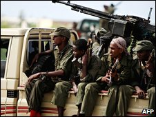 Somali government soldiers ride in the back of a pick-up truck in Mogadishu, 14 September 2009