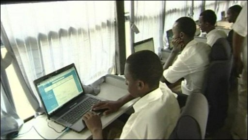 Schoolchildren using modern laptops with web connection in a Rwandan school bus