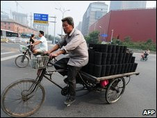 A man delivering bricks of coal on his tricycle in Beijing on 16 September, 2009