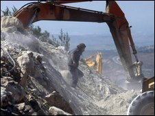 A settler walks past an earthmover preparing the ground for housing near the West Bank city of Nablus