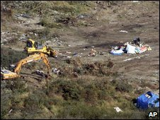 Bulldozers clear the makeshift camp in Calais after migrants were evacuated in Calais,22 September 2009