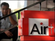 A man talks on his mobile phone next to a Bharti Airtel sign