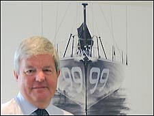 Sir Keith Mills in front of a photo of his personal boat