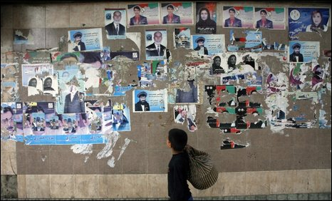 An Afghan boy walks past election posters for presidential and provincial council candidates in Kabul, Afghanistan Wednesday, Sept. 16, 2009.