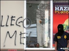 """A policeman stands outide a sandwich shop scrawled with the words """"Mel arrived"""""""