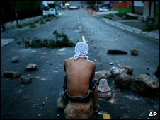 A protester sits on a rock at a road block in Teugcigalpa