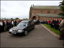 Mourners gather as coffin passes