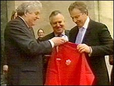 Rhodri Morgan gives Tony Blair a Welsh rugby shirt, watched by Welsh Secretary Peter Hain, in Swansea in 2005