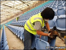 Cleaners wipe dust off seats at the ANZ stadium following the storm that swept through Sydney, 24 Sept