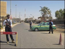 Iraqi police stand guard at a checkpoint in Tikrit