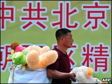 Toy seller in front of government slogan, Beijing, July 09