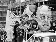 Carnival heads representing National Front leaders John Tyndall (right) and Martin Webster flanking Adolf Hitler on a lorry in a procession