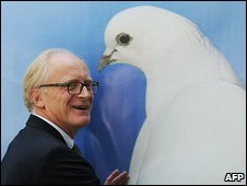 United Nations special envoy to Afghanistan Kai Eide hugs a picture of a dove during a press conference at the UNAMA office in Kabul on September 16, 2009