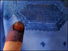 This file picture taken on August 20, 2009 shows a burqa-clad Afghan woman displaying her finger marked with indelible ink after casting her vote at a polling station in Kabul