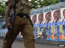 A Sri Lankan policeman passes a poster portraying president Mahinda Rajapakse in Colombo on May 20, 2009