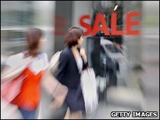 Shoppers walk past Sale sign