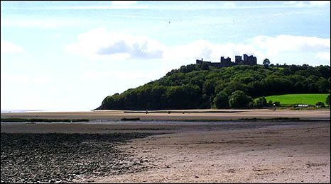 Image of Llansteffan Castle in the distance with the beach in the foreground by Peter Jackson.