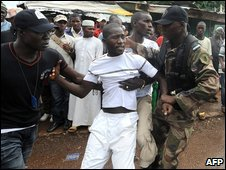 Police arrest a protester in Conakry, Guinea (28 September 2009)