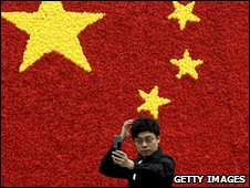 A man prepares his hair in front of a Chinese flag in Beijing