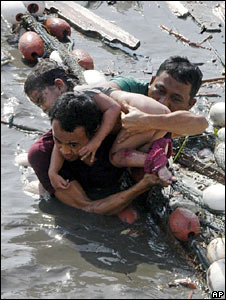 A man, assisted by his friend, carries his injured daughter after the tsunami hit Aceh, Indonesia. Photo: 26 December 2004