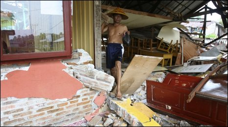Man walks through rubble of collapsed school