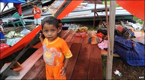 A boy stands outside a tent next to his destroyed home (background) after an earthquake in Padang, Sumatra