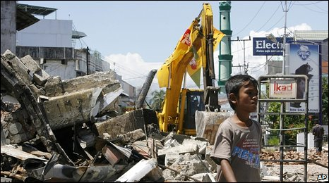 A boy walks past a shattered building in Padang, 2 October 2009