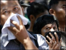 People cover their noses as they watch a search in Padang, 2 October 2009