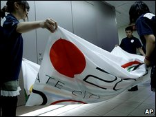 In Tokyo, workers fold up the city's Olymopic bid banner