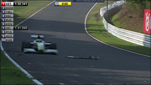 Jenson Button drives through debris