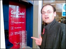 Blogger James Watson in front of a coin cashing machine