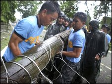 Local police move an electricity pole knocked over by Typhoon Parma in Tuguegarao City, Luzon island