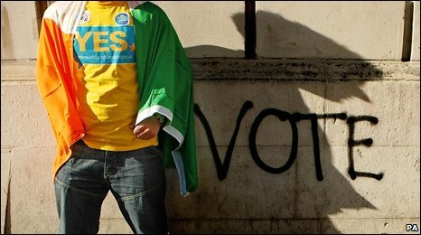 "A ""Yes"" supporter draped in the Irish flag beside graffiti at Dublin Castle, 3 October 2009"