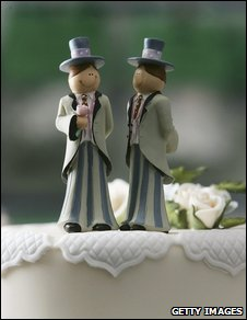 A professionally-taken photo of a wedding cake with two grooms