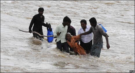 Villagers wade through flood waters in Andhra Pradesh on October 6, 2009