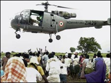 Flood victims rush for food packets being dropped from an Indian air force helicopter at a village in Mehbubnagar in Andhra Pradesh on Oct 5, 2009