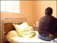 Man sitting on bed in mental health unit