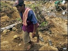 A villager walks in an area hit by quake-triggered landslide in West Sumatra.